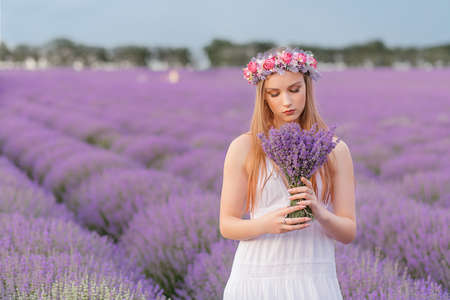 Beautiful woman admires a bouquet of lavender in a sunset, lavender field 写真素材