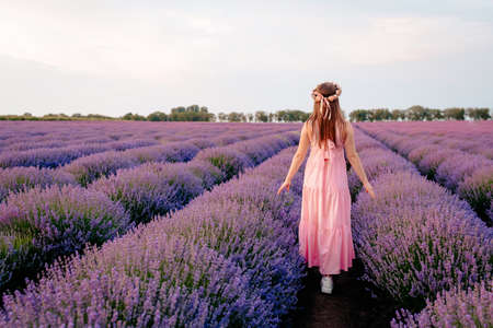 A girl in a pink dress walks on a lavender field
