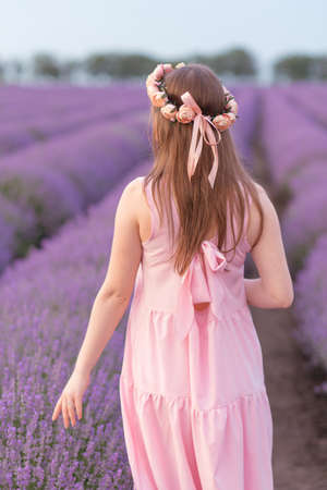 A woman walks in a lavender field enjoying the sight and smell 写真素材