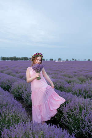 Beautiful woman with a bouquet of lavender in a lavender field