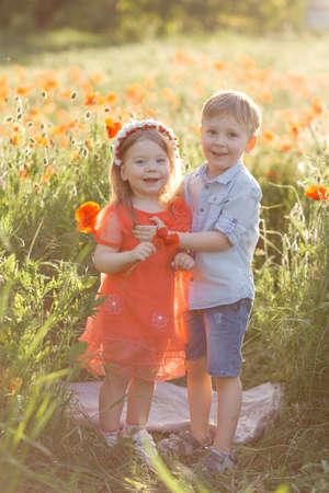 Happy boy and girl play in poppy field