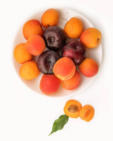 Juicy ripe apricots and plums with a green leaf on a plate close-up, on a white background
