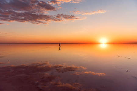 A lonely man walks on the beach at sunset Stockfoto