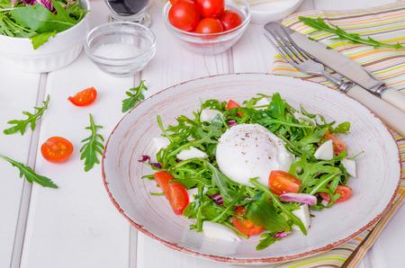 Fresh salad with arugula, mozzarella, cherry tomatoes and poached egg