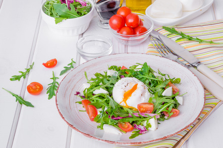 Fresh salad with arugula, mozzarella, cherry tomatoes and poached egg