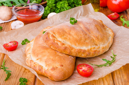 Pizza Calzone with tomato sauce, cheese, herbs, mushrooms and sausages