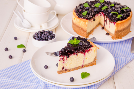 Delicious cream cheesecake with lemon zest and blueberry jam 스톡 콘텐츠