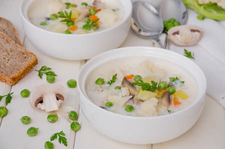 Cheese cream soup with cauliflower and green peas