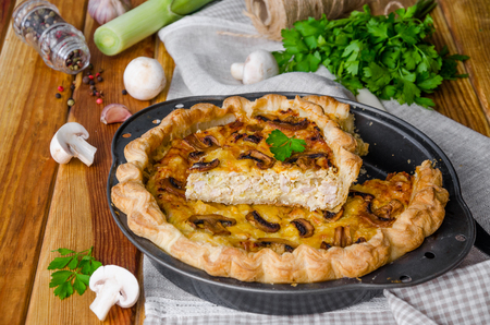 Quiche on puff pastry with leek, meat and mushrooms.
