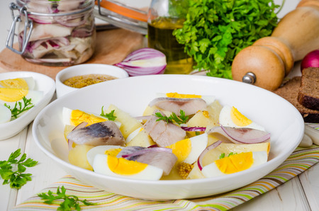Potato salad with salted fish, boiled eggs, onions and parsley leaves.