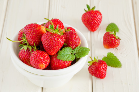 Fresh ripe strawberries in a bowl on a white wooden background. Imagens