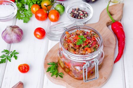 Eggplant caviar with tomatoes and roasted bell pepper in a glass jar