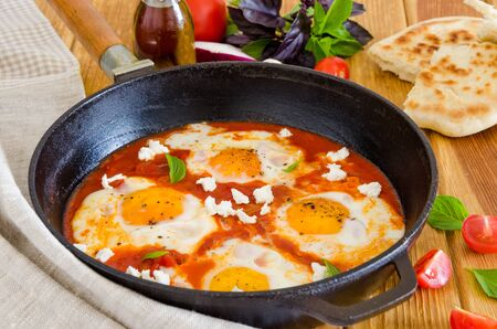 Shakshouka, dish of eggs poached in a sauce of tomatoes, chili, onions in the pan.