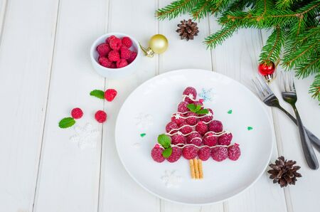 Raspberry Christmas tree on a white plate with white chocolate and icing sugar. Christmas food idea. Healthy dessert. Stok Fotoğraf