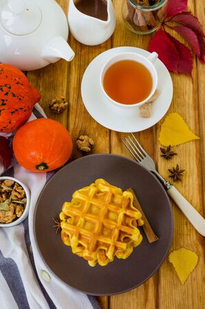 Stack of spicy pumpkin waffles on a dark plate with caramel sauce and whipped cream on a dark wooden background. Rustic style. Fragrant autumn breakfast. Breakfast for Halloween. 版權商用圖片