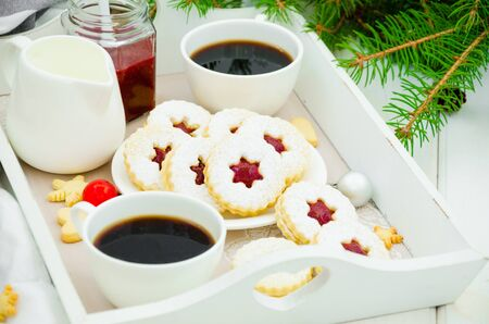 Christmas Linzer cookies filled with strawberry jam on a white plate on a tray with two cups of coffee. Morning Christmas, Christmas breakfast. Imagens