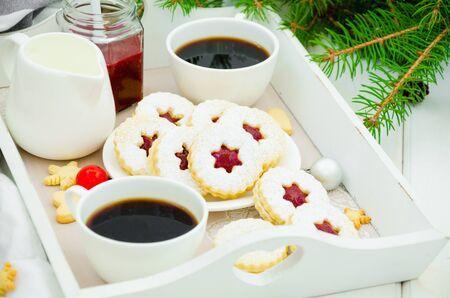 Galletas Linzer de Navidad llenas de mermelada de fresa en un plato blanco en una bandeja con dos tazas de café. Mañana de Navidad, desayuno de Navidad. Foto de archivo