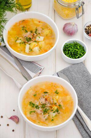 Zuppa fatta in casa con verdure, tonno in scatola e semola di mais in una ciotola su uno sfondo di legno bianco. Un pranzo veloce ed economico per tutta la famiglia.