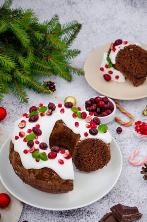 Chocolate cake Christmas wreath with sugar icing, cranberries, pomegranate and mint leaves on top. Festive Dessert for Christmas and New Year.