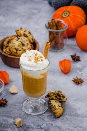 Pumpkin latte in a glass with spicy cream and a cinnamon stick on a gray stone background with cookies with chocolate chips. Autumn drink. Thanksgiving drink. Reklamní fotografie