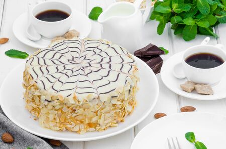 Esterhazy traditional cake with almonds and pralines on a white wooden background on a plate with a cup of coffee. Hungarian, Austrian cuisine. Фото со стока
