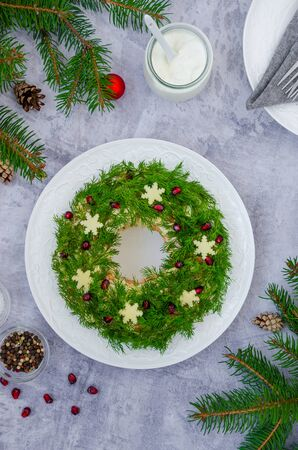 Olivier salad Christmas wreath with vegetables, meat (sausage), eggs and mayonnaise on a plate on a gray background. Traditional festive Russian and Ukrainian salad for Christmas and New Year.