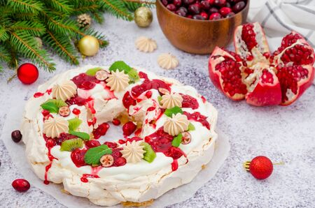 Caramel Pavlova Christmas wreath with cherry sauce, pomegranate, cranberries and kiwi on a light stone background. Festive dessert for Christmas and New Year. Stock Photo