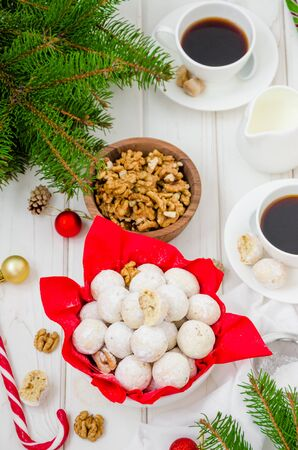 Homemade snowballs cookies with walnuts in icing sugar in a bowl on a white wooden background. Dessert for Christmas and New Year. Vertical orientation. Top view. Stock Photo