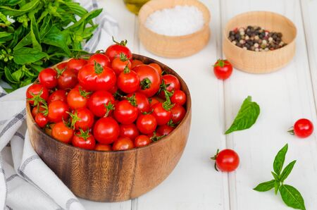 Ingredients for summer vegetable salad with cherry tomatoes, basil herb, olive oil and salt in on a wooden bowl white wooden background. Rustic style. Stock fotó