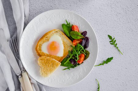 Piece of bread toast cut in shape of heart with egg on a white plate with arugula and cherry tomatoes. Romantic breakfast for Valentines Day. Top view. Horizontal orientation.
