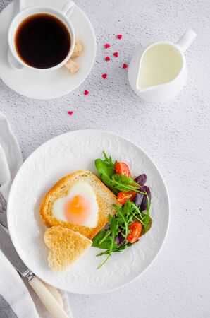 Piece of bread toast cut in shape of heart with egg on a white plate with arugula and cherry tomatoes. Romantic breakfast for Valentines Day. Top view. Vertical orientation.