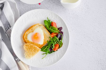 Piece of bread toast cut in shape of heart with egg on a white plate with arugula and cherry tomatoes. Romantic breakfast for Valentines Day. Top view. Copy space. Horizontal orientation. Banco de Imagens