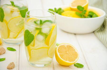 Limonada casera con rodajas de limón, menta y azúcar morena en un vaso con hielo sobre un fondo de madera blanca. Orientación horizontal.