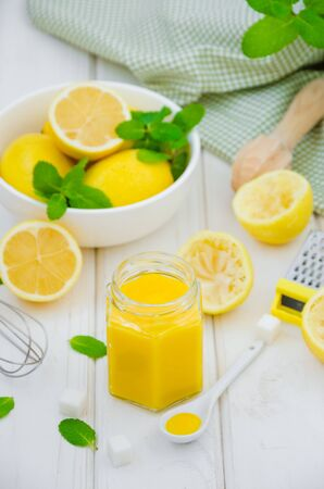 Homemade Lemon curd in glass jar with fresh lemons on a white wooden background. Vertical orientation.