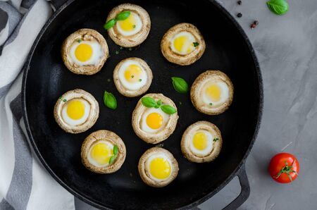 Baked stuffed mushrooms with quail eggs with thyme leaves and basilin in an old cast-iron frying pan on a dark concrete background. Easter appetizer. Horizontal orientation. Top view
