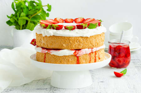 Victoria sponge cake with strawberry jam, whipped cream and fresh strawberries on top on a white plate on a wooden background. Horizontal orientation, copy space