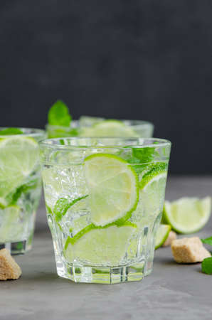 Fresh summer mojito drink with lime slices, mint, ice cubes and brown sugar in a glass on a dark background. Horizontal, copy space 免版税图像