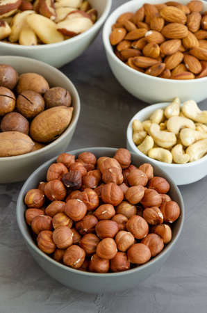 Hazelnuts, almonds, Brazilian nuts, cashews, macadamia, pecans and pistachios in bowls on a dark concrete background. Healthy food. Vertical, copy space
