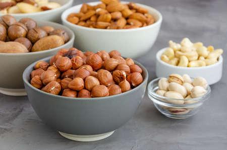 Hazelnuts, almonds, Brazilian nuts, cashews, macadamia, pecans and pistachios in bowls on a dark concrete background. Healthy food. Horizontal, copy space Stock fotó