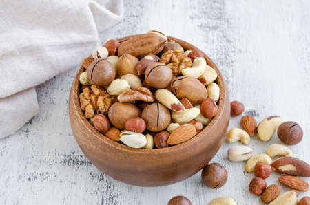 Mix of nuts in a wooden bowl on a light wooden background. Healthy food concept. Horizontal, selective focus