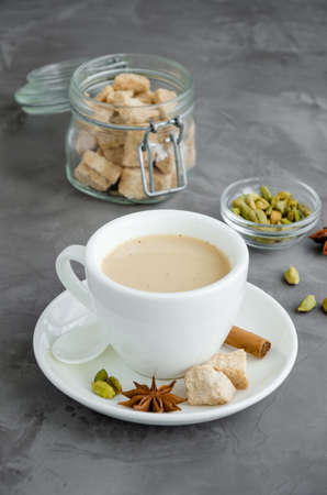 Hot tea with milk, cinnamon, cardamom, anise and other spices, Indian masala tea in a white cup on a dark background. Vertical, copy space