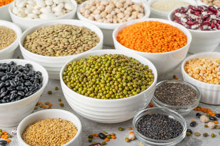 Mix of legumes, chickpeas, lentils, beans, peas, quinoa, sesame, chia, flax seeds in bowls on a gray concrete background Stockfoto