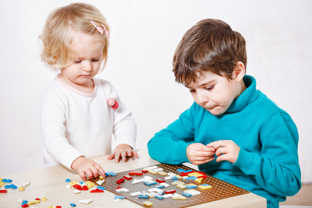 assiduous: kid playing with educational toys on a table