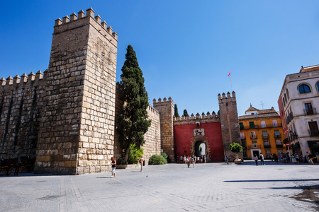 real renaissance: Sevilla, Spain - September 09, 2015:  View to the gate to Real Alcazar Gardens in Seville. Tourists walking on sunny streets. Spain Editorial