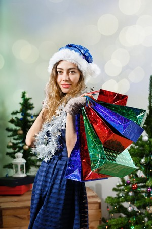 broadly: Portrait of a happy woman in blue santa hat  with shopping present bags