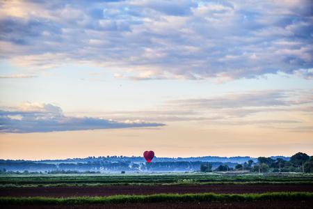 Red air balloon heart rises up at dawn