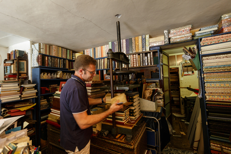 The owner and visitor are kindly discussing the restoration of books. Venice Editorial