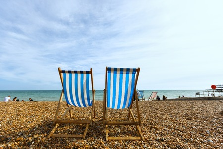 Two empty striped folding beach chairs on seacoast in Brighton, unknown people Reklamní fotografie