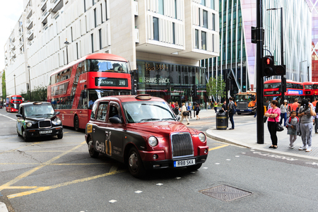 Legendary London taxi cab and red bus on the streets of London Foto de archivo - 106771899