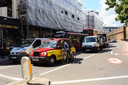 cyclist talks through a car window with taxi driver at a crossroads of London